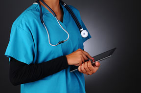 Closeup of a female medical professional wearing scrubs taking notes on a tablet computer. Horizontal format on a light to dark gray background. Woman is unrecognizable.
