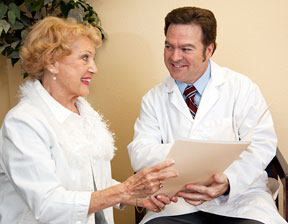 Friendly doctor sitting beside his patient, going over her chart.